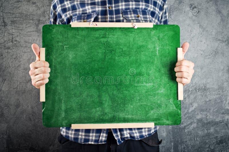 Hombre que sostiene la pizarra verde fotografía de archivo