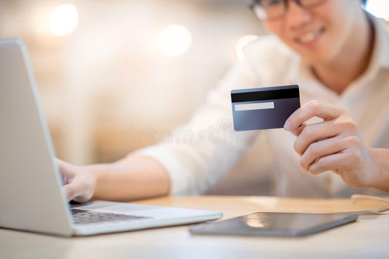 Hombre que sostiene la tarjeta de crédito para las compras en línea fotografía de archivo