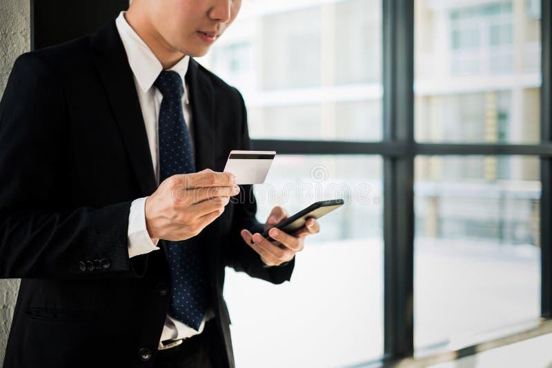 Hombre que sostiene la tarjeta de crédito y que usa página web de las compras del ordenador portátil y del smartphone en línea, c foto de archivo libre de regalías