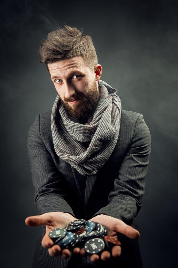 Hombre que sostiene las fichas de póker foto de archivo libre de regalías
