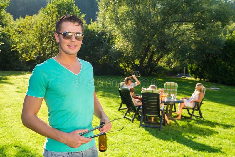 Hombre que sostiene las pinzas y la botella de vino en la fiesta de jardín fotos de archivo