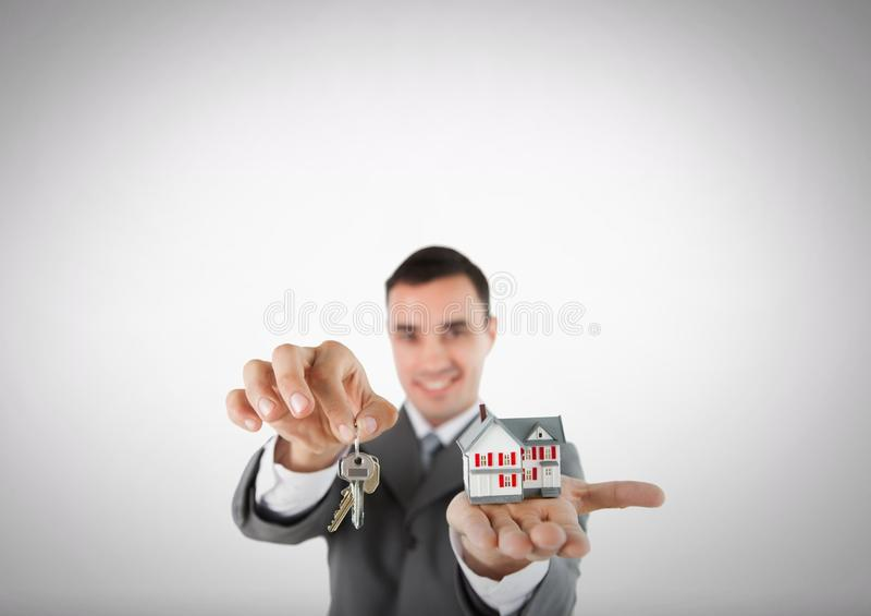 Hombre que sostiene llave y la casa delante de la ilustración imágenes de archivo libres de regalías