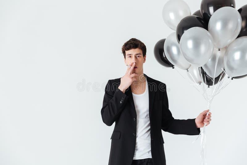 Hombre que sostiene los balones de aire y que fuma el cigarrillo fotografía de archivo libre de regalías