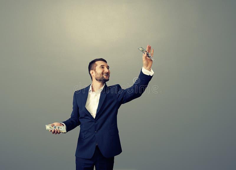 Hombre que sostiene los billetes sobre fondo oscuro foto de archivo libre de regalías