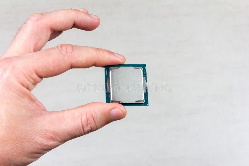 Hombre que sostiene los fingeres falsos encima de la 8va GEN del procesador de escritorio en el primer gris del fondo imágenes de archivo libres de regalías