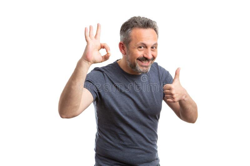 Hombre que sostiene los fingeres tan muy bien y como gesto imagenes de archivo
