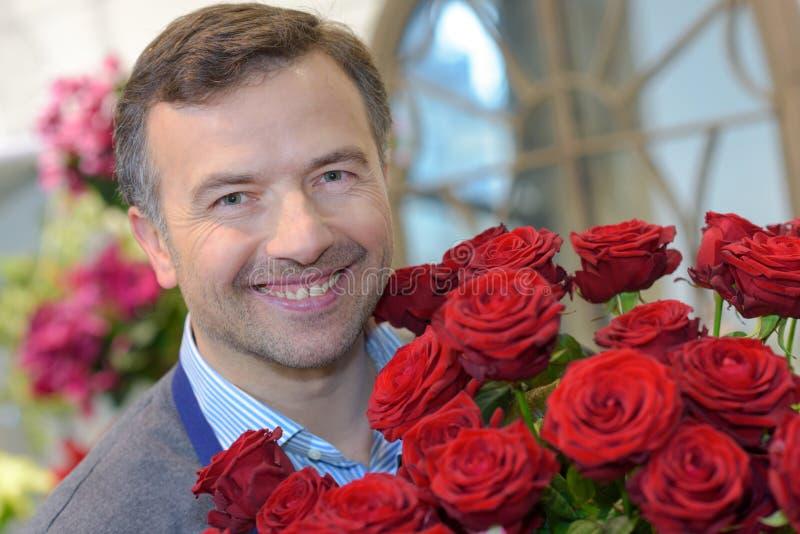 Hombre que sostiene rosas del ramo imagenes de archivo