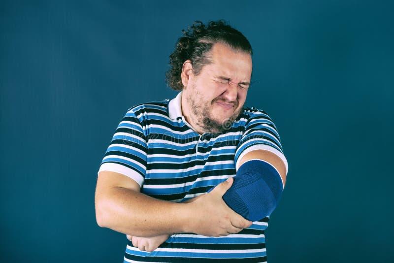 Hombre que sostiene su codo dolorido Problemas de salud fotos de archivo libres de regalías