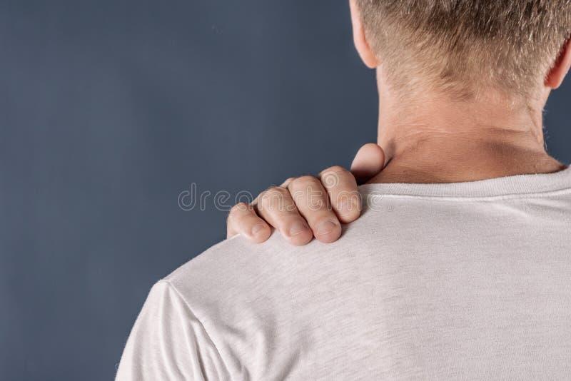 Hombre que sostiene su hombro dolorido que intenta aliviar dolor en fondo azul Problemas de salud fotografía de archivo libre de regalías