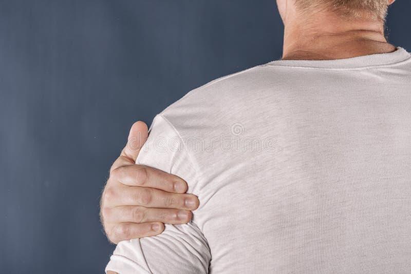 Hombre que sostiene su hombro dolorido que intenta aliviar dolor en fondo azul Problemas de salud imagen de archivo libre de regalías