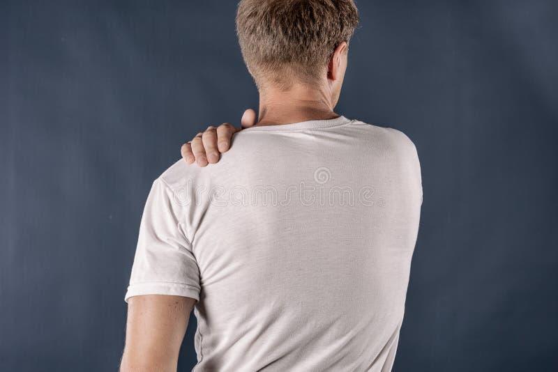 Hombre que sostiene su hombro dolorido que intenta aliviar dolor en fondo azul Problemas de salud foto de archivo