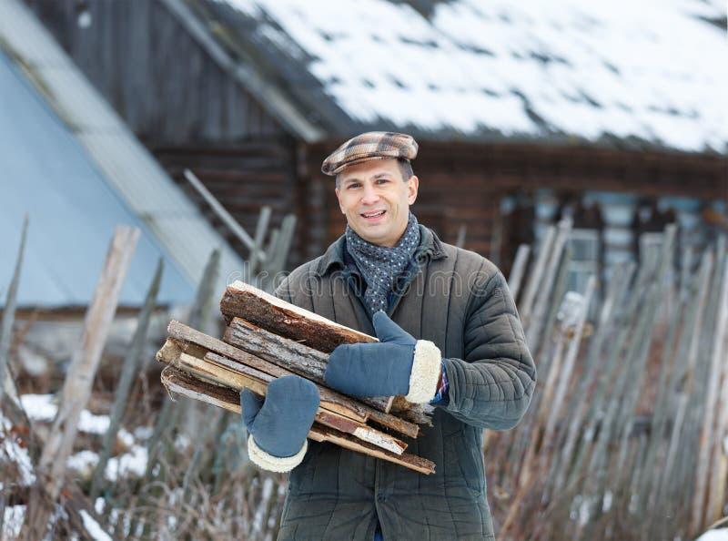 Hombre que sostiene un brazado de leña fotografía de archivo