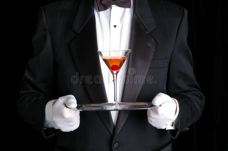 Hombre que sostiene un coctel en la bandeja de plata imagenes de archivo