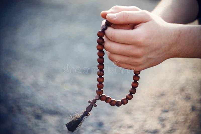 Hombre que sostiene un rosario de madera y que ruega fotografía de archivo