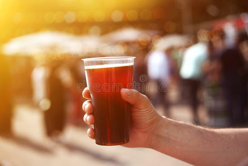 Hombre que sostiene un tarro de cerveza oscura en su mano en el festival de la calle de la cerveza y de la comida foto de archivo libre de regalías