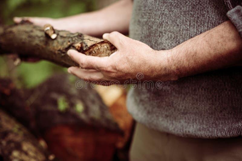 Hombre que sostiene un tronco de árbol fotos de archivo