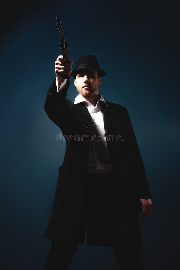 Hombre que sostiene una arma de mano fotos de archivo libres de regalías