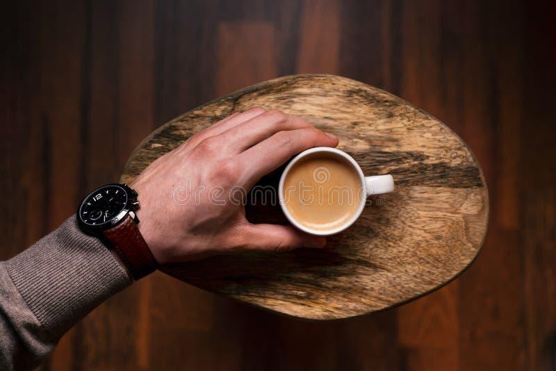 Hombre que sostiene una taza de café en un de madera, fondo del vintage Mano del hombre de negocios joven que sostiene una taza d fotografía de archivo