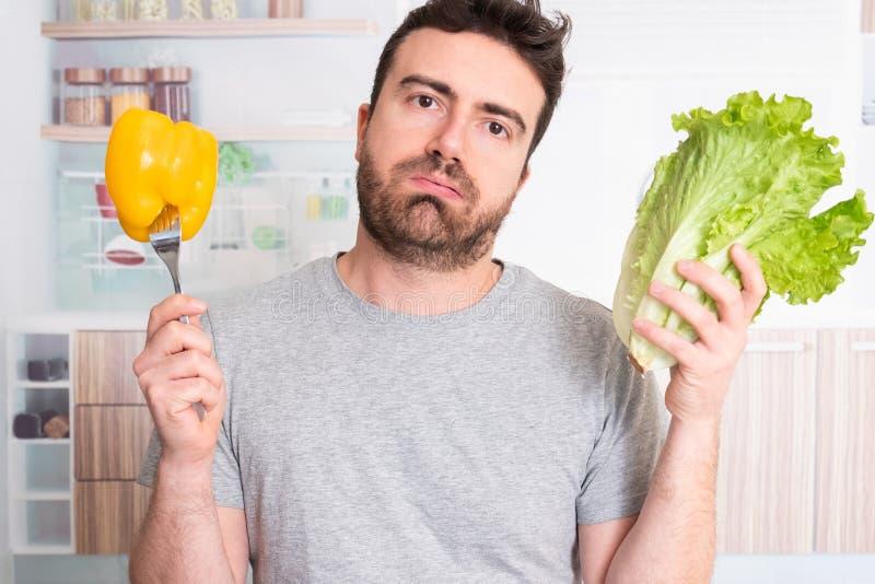 Hombre que sostiene verduras en la cocina fotos de archivo