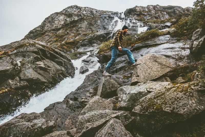 Hombre que sube en cascada de las montañas rocosas foto de archivo libre de regalías