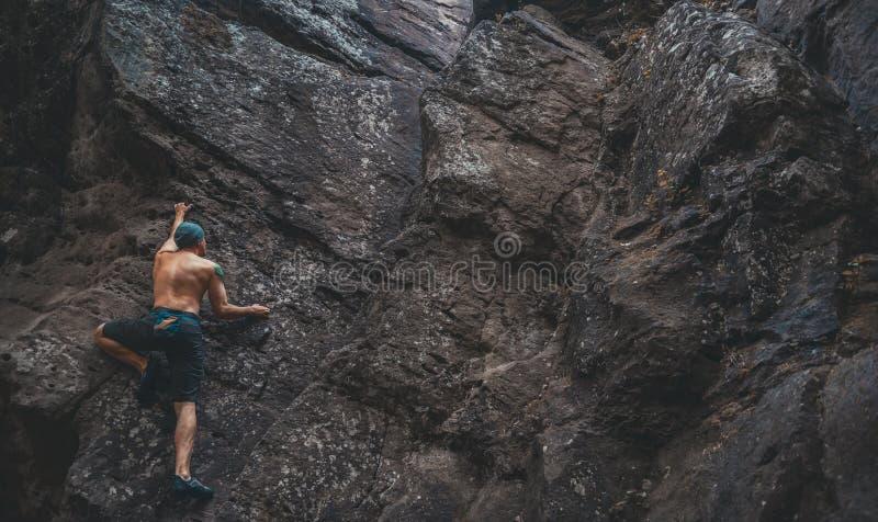Hombre que sube en la roca de piedra foto de archivo