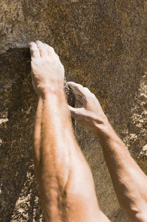 Hombre que sube en roca foto de archivo libre de regalías