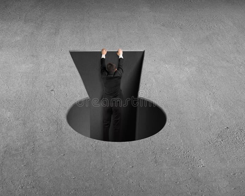Hombre que sube hacia fuera del agujero dominante de la forma imagenes de archivo