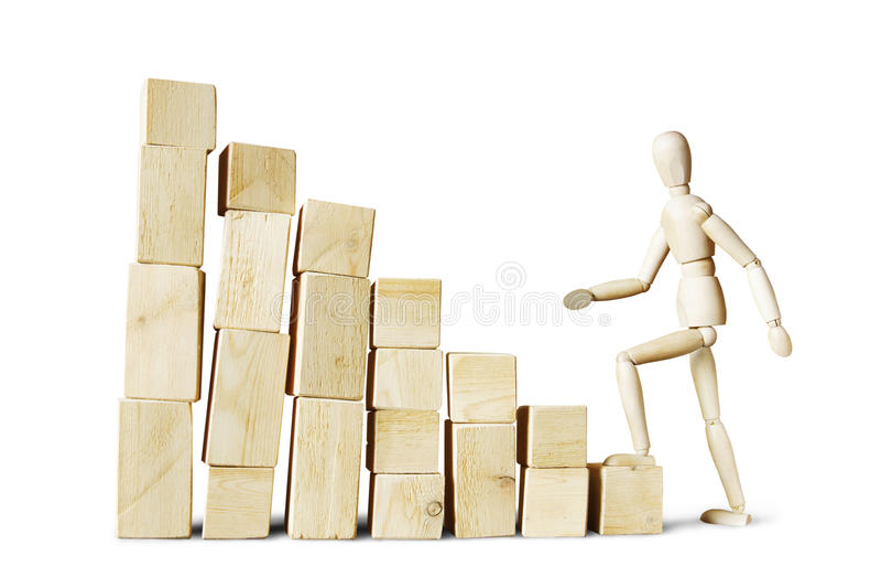 Hombre que sube hasta la alta pila de bloques fotografía de archivo libre de regalías