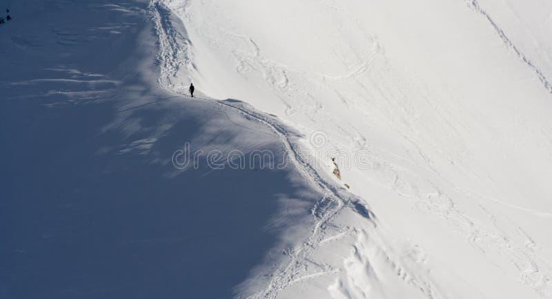 Hombre que sube la montaña nevosa foto de archivo