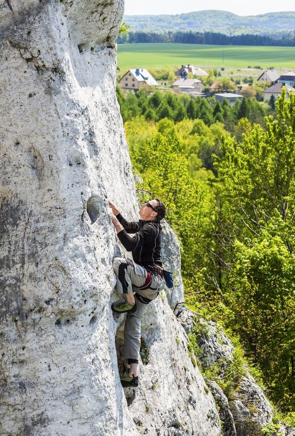 Hombre que sube la pared rocosa natural foto de archivo