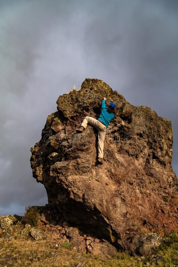 Hombre que sube una roca fotografía de archivo