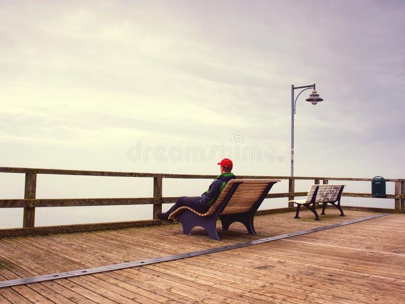 Hombre que sueña la sentada en un embarcadero de madera cerca del agua fotografía de archivo libre de regalías