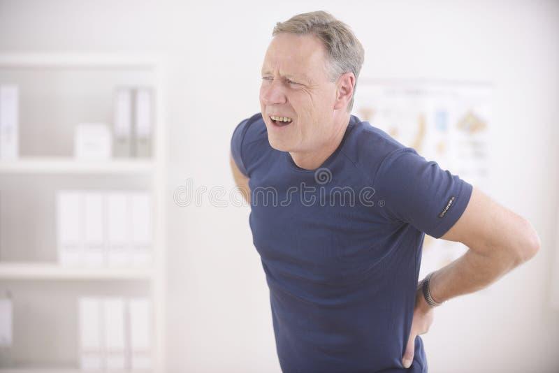 Hombre que sufre de dolor de espalda fotografía de archivo libre de regalías