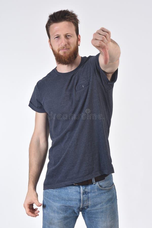 Hombre que sujeta su pulgar hacia abajo y serio en el fondo blanco, serio imagen de archivo