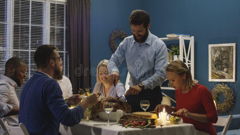 Hombre que talla el pavo en cena del día de fiesta imagen de archivo libre de regalías