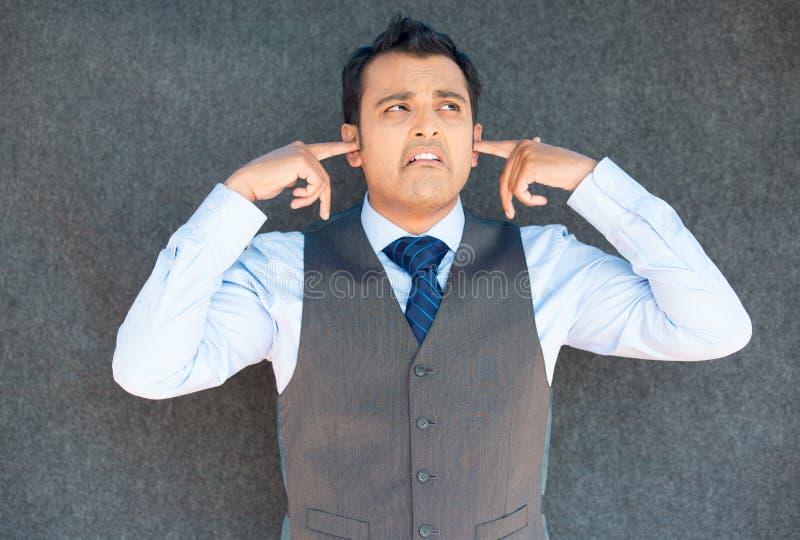 Hombre que tapa los oídos para el fuerte ruido imagen de archivo