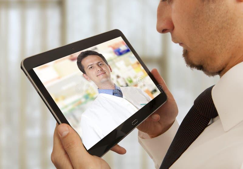 Hombre que tiene charla video con el doctor imagen de archivo