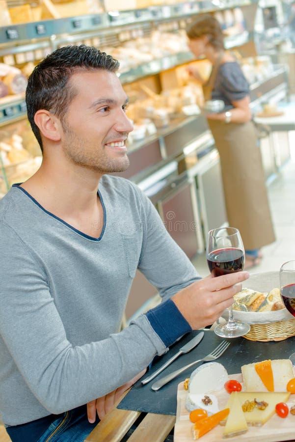 Hombre que tiene comida que sostiene el vino rojo de cristal fotografía de archivo libre de regalías