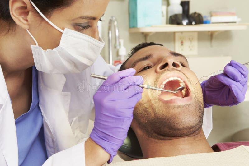 Hombre que tiene control para arriba en la cirugía de los dentistas foto de archivo libre de regalías