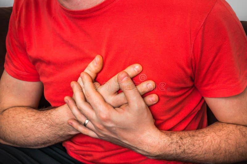 Hombre que tiene dolor de pecho, ataque del corazón fotografía de archivo