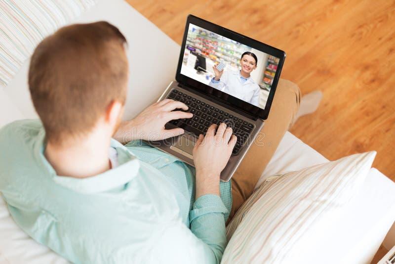 Hombre que tiene llamada video con el farmacéutico en el ordenador portátil foto de archivo
