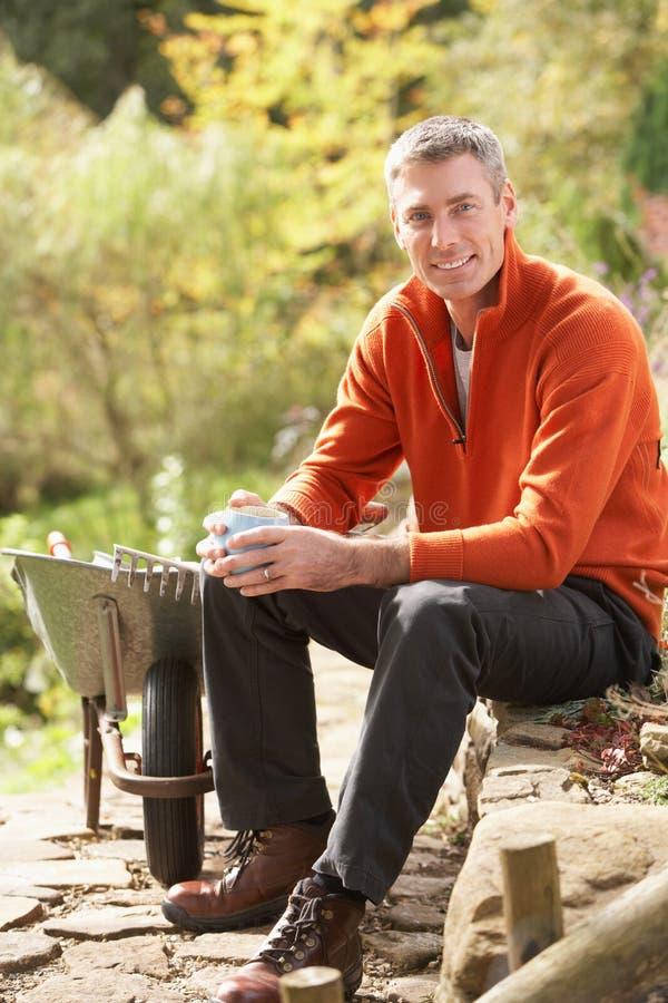 Hombre que tiene rotura mientras que trabaja en jardín fotos de archivo