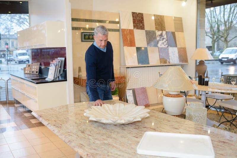 Hombre que toca diversos finales en tienda moderna de la cocina imagen de archivo