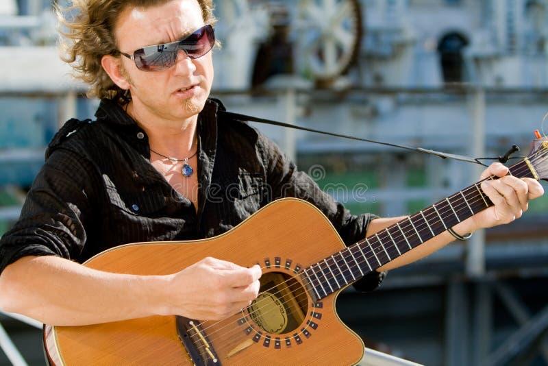 Hombre que toca la guitarra acoutic imagen de archivo libre de regalías