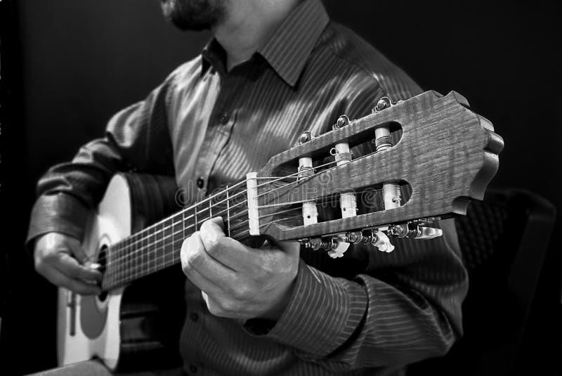 Hombre que toca la guitarra clásica en blanco y negro imagen de archivo