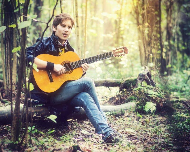 Hombre que toca la guitarra en bosque imagen de archivo