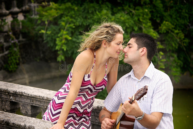 Hombre que toca la guitarra para su mujer foto de archivo libre de regalías