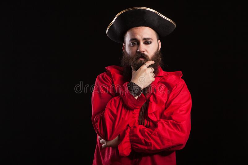 Hombre que toca su barba y que parece un pirata bárbaro para Halloween fotos de archivo libres de regalías