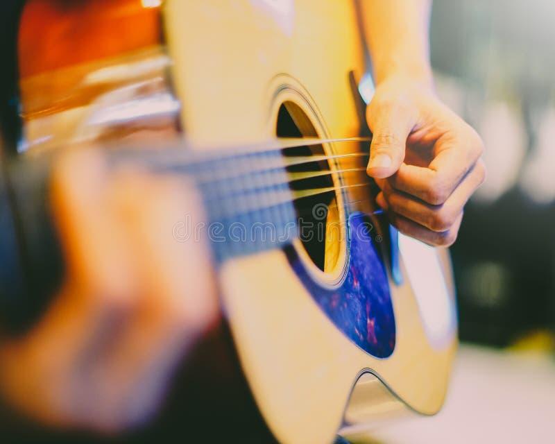 Hombre que toca una guitarra acústica fotografía de archivo