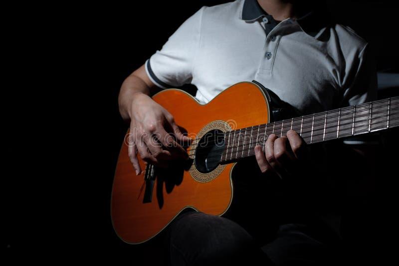 Hombre que toca una guitarra acústica en un fondo oscuro Tocar la guitarra foto de archivo libre de regalías